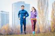 Leinwanddruck Bild - Urban jogging - couple running in autumn city on a hill