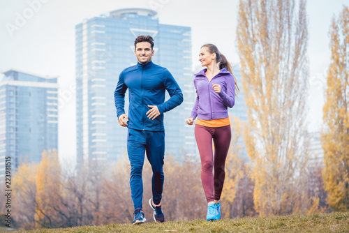 Leinwanddruck Bild Urban jogging - couple running in autumn city on a hill