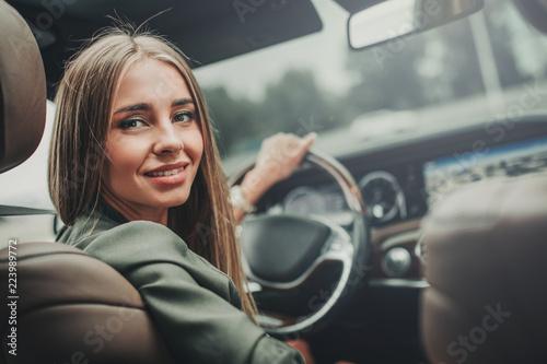 Leinwandbild Motiv Portrait of optimistic pretty girl holding steering wheel while looking at camera. She locating in vehicle