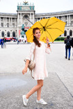 VIENNA, AUSTRIA. A girl with a yellow umbrella on the background of the Neue Burg, a new castle of the Hofburg Palace. Museum in Heldenplatz. - 223998988