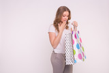 Portrait of young happy smiling woman with shopping bags on white background with copy space - 224038309