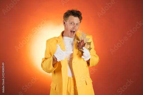 Crazy man are preparing for autumn day. Surprise man playing with leaves and looking at camera. Funny man advertises your goods and services. Isolated object on orange background. Funny fashion Man. - 224080549