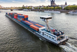 A large barge loaded with shipping containers floating on the river Rhine in Cologne. - 224093706