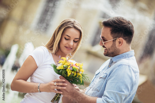 Leinwandbild Motiv Picture of young man surprising woman with flowers