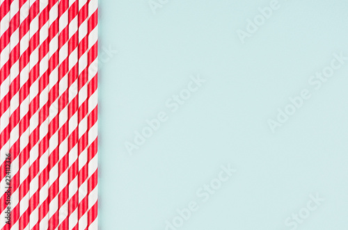 Funny festive bright abstract background - striped red cocktail straws on pastel candy mint color backdrop.