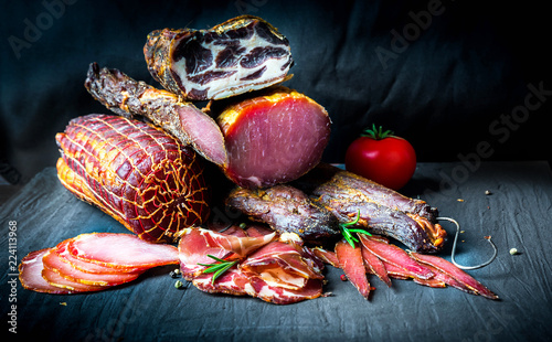 A set of different types of raw smoked meat. Jamon Lomo, сoppa and fillet on a black background. - 224113968