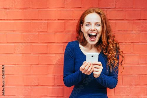 Leinwanddruck Bild frau mit mobiltelefon steht vor einer roten wand und freut sich