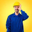 Young workman with helmet makes funny and crazy face emotion on yellow background