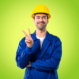 Young workman with helmet happy and counting two with fingers on green background - 224137120