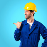 Young workman with helmet pointing to the side with a finger to present a product or an idea while looking forward smiling on blue background - 224137184