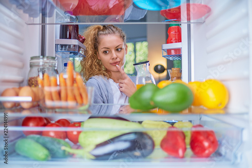 Woman standing in front of opened fridge and choosing what to eat for breakfast. Fridge full of groceries.