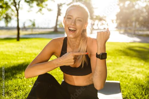 Leinwanddruck Bild Cheerful young sports woman outdoors sitting on grass