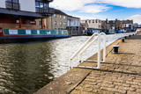 White Ladder and Bollards on a Cobblestone Quay along a Canal in Edinburgh on a Sunny Winter Morning - 224156192