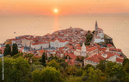 Wall mural Romantic colorful sunset over picturesque old town Piran with sun on the background, Slovenia. Scenic panoramic view.