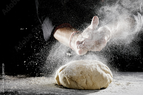 Man sprinkling white flour over blob of dough