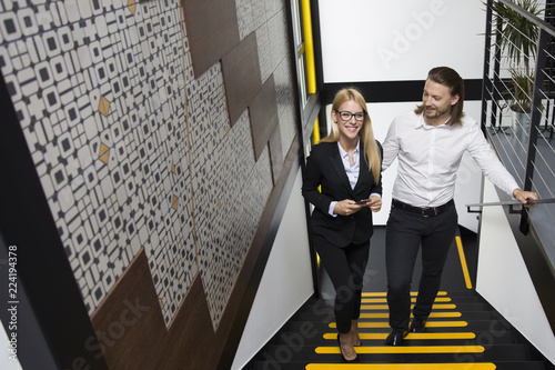 Foto Murales Young business people climbing up stairs in modern office