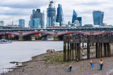 Volunteers cleaning the shores of the Thames from waste during low tide, Southbank, London