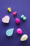 Cosmetic sponges of different colors and different shapes on purple background. - 224213533