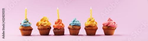 Tasty cupcakes on pinke background. Birthday cupcake in rainbow colors.
