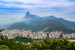Quadro View of city Rio de Janeiro with Favelas in the hills with misty statue on mountain