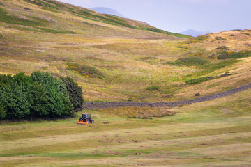 Scenic English countryside and an agricultural tractor mowing grass for hay in a farmland in a distance