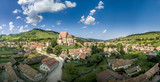 Aerial panorama view of Biertan fortified church, seat of the Saxon bishop in Transylvania, with triple ring of walls, towers, matrimony room blue cloudy sky background