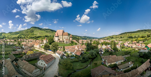 Foto Murales Aerial panorama view of Biertan fortified church, seat of the Saxon bishop in Transylvania, with triple ring of walls, towers, matrimony room blue cloudy sky background