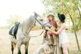 Beautiful young girl with blond hair in a suede jacket with fringe with little sister in a straw hat and checkered vintage dress with a horse in the countryside on a sunny autumn day