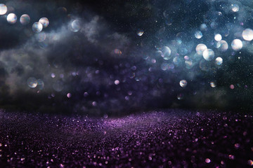 glitter vintage lights background. black, blue, purple and silver. de-focused.
