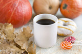 1 white Cup of coffee among pumpkins, one Donat with icing, lollipops, dry oak leaves - 224303918
