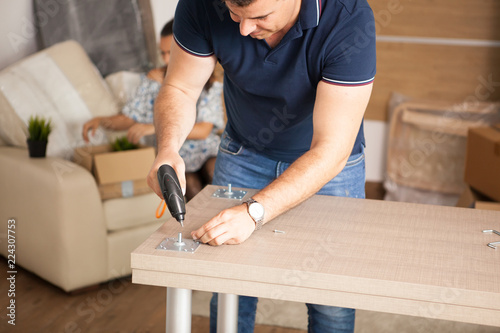 Leinwanddruck Bild Man is working with furniture assembly using electric screwdriver in new house.Man using tools.