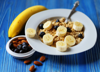 Healthy eating, food and diet concept - oatmeal with berries, nuts and bananas, white plate, blue wooden background.