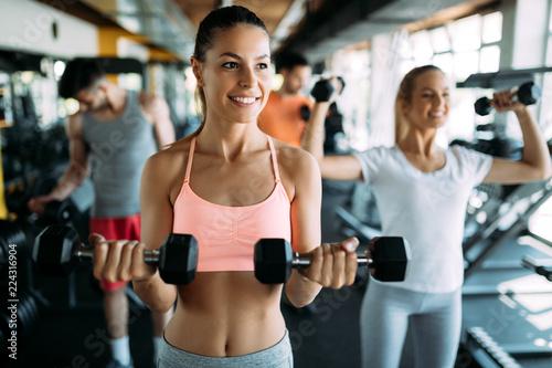 Młoda kobieta robi ćwiczeniu z dumbbell w gym