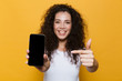 Happy cute young woman posing isolated over yellow background showing display of mobile phone.