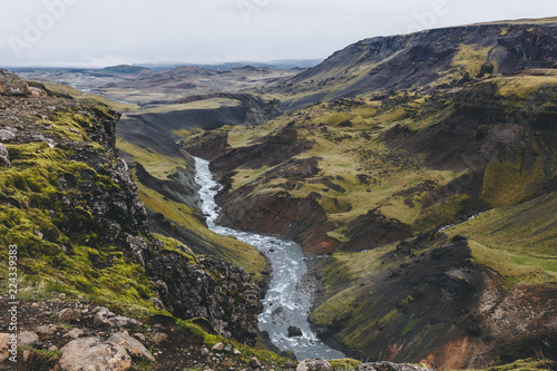 aerial view of curvy river streaming in green hills in Iceland on cloudy day - 224339383