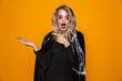Quadro Surprised woman wearing black costume and halloween makeup holding copyspace on palm, isolated over yellow background