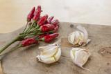 Peperoncini rossi e aglio in camicia sul tagliere - 224340778