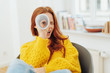 redhead woman looking through paper telescope