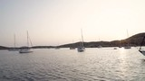 Boats and yacht sailing in the sea in Cyclades islands in Greece at sunset, for vacation and trip - 224352311