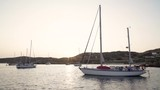 Moored Boats and yacht in the sea of Cyclades islands in Greece at sunset, for vacation and trip - 224357947