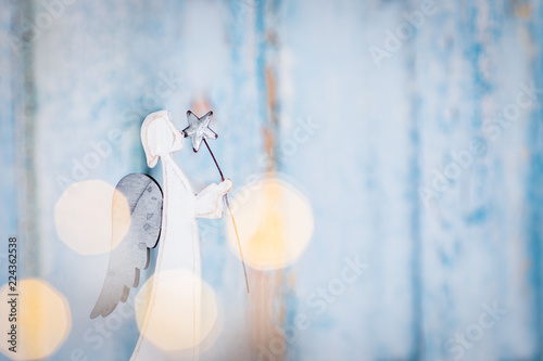 White angel Christmas decoration on blue background with lights - 224362538