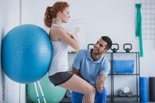 Leinwandbild Motiv Smiling professional personal trainer helping sportswoman exercising with ball