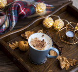 Cup of coffee or hot chocolate in a wooden tray, autumn cosy scarf and decorations - 224393329