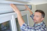 man installing cassette roller blinds on windows