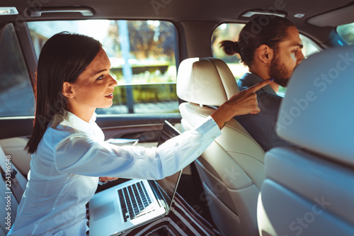 Chauffeur driven limousine with the business woman in the back seat - 224396548