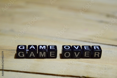 Game over message written on wooden blocks. education and motivation concepts. Cross processed image on Wooden Background