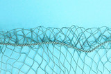 Fishing net with space for your text. Blue background for a fishery theme. - 224429562