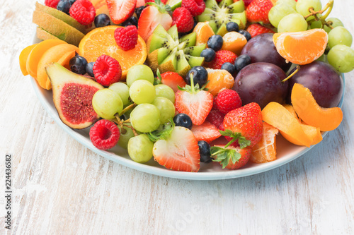Foto Murales Healthy fruit platter, strawberries raspberries oranges plums apples kiwis grapes blueberries on the white wooden table, copy space for text, selective focus