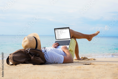 Foto Murales Man reading email on laptop while relaxing on beach