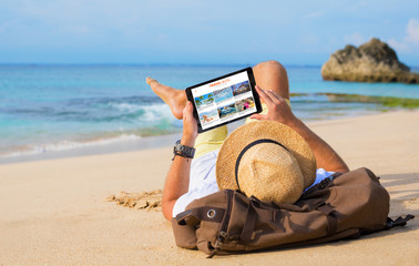 Man reading travel blog on beach